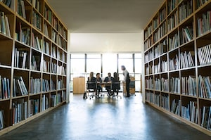 Group of people in library with shelves of books